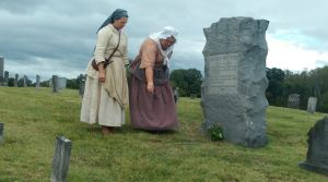 Pam Eddy and Lisa Bennett pouring black powder of Mary Patton's grave